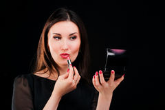 Young woman applying lipstick looking at mirror. On black Royalty Free Stock Image
