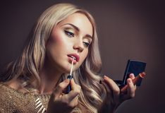 Young woman applying lipstick looking at mirror. Portrait of a woman making up Royalty Free Stock Images