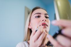 Young woman applying lipstick looking at mirror.  Royalty Free Stock Images