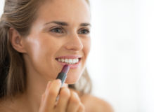 Young woman applying lipstick Royalty Free Stock Images