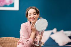 Woman applying a lipstick at home. Young woman applying a lipstick sitting with a mirror in the beautiful blue bedroom at home Royalty Free Stock Photo