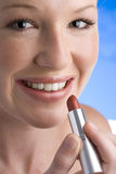 Young woman applying lipstick, smiling, portrait, close-up Stock Photos