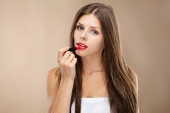 Young woman applying lipstick Stock Photo