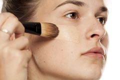 Woman applying foundation. Young woman applying liquid foundation with brush on a white background royalty free stock photo