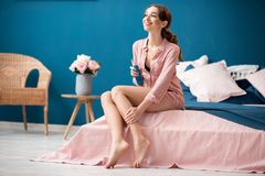 Woman applying skin lotion indoors. Young woman applying a lotion on her legs sitting on the bed in the beautiful pink and blue bedroom interior Royalty Free Stock Photo