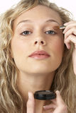 Young Woman Applying Make-Up Royalty Free Stock Image