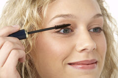 Young Woman Applying Make-Up Stock Images
