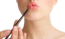 Young woman applying make up on lips Royalty Free Stock Photography