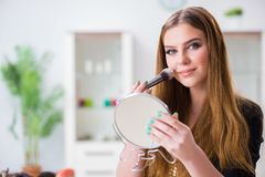 The young woman applying make-up preparing for party. Young woman applying make-up preparing for party stock image