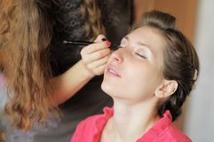 Young woman applying make-up by professional make-up artist Royalty Free Stock Images