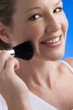 Young woman applying make-up, smiling, portrait Royalty Free Stock Images