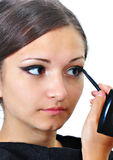 Young woman applying makeup. To herself and looking in the mirror royalty free stock photo