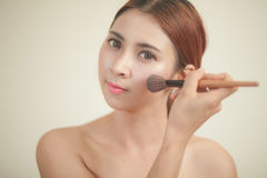 Young woman applying makeup Stock Photos