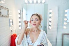 Young woman applying makeup at home Royalty Free Stock Photo