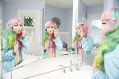Young woman applying makeup with multiple mirror reflections Royalty Free Stock Images