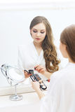 Young woman applying makeup in a studio Royalty Free Stock Photography