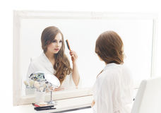Young woman applying makeup in a studio Stock Image