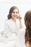 Young woman applying makeup in a studio Royalty Free Stock Photo