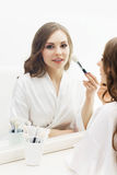 Young woman applying makeup in a studio Stock Images