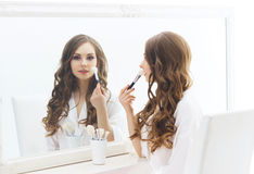 Young woman applying makeup in a studio Stock Photos