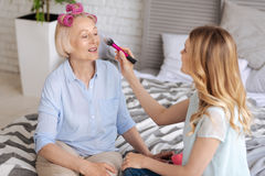 Young woman applying makeup to her mother. Meticulous preparations. Pleasant fair-haired women being about to apply some makeup to the face of her mother while Stock Images