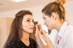 Young woman applying makeup to model in salon Royalty Free Stock Photo
