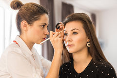 Young woman applying makeup to model in salon Stock Photos