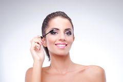 Young woman applying mascara. Bare shoulders Royalty Free Stock Photo