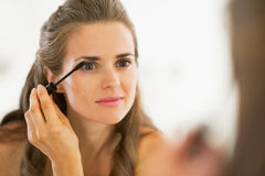 Young woman applying mascara in bathroom. Young pretty woman applying mascara in bathroom Stock Image