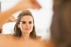 Young woman applying mascara in bathroom Stock Photography