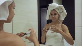 Young woman applying mascara on eyelashes in the bathroom. stock footage