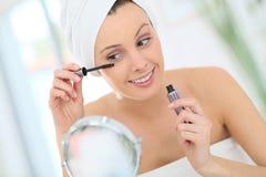 Young woman applying mascara on her eyelashes Royalty Free Stock Image