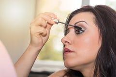 Young woman applying mascara on her eyelashes, light effect. Pretty young woman applying mascara on her eyelashes, light effect Royalty Free Stock Photos
