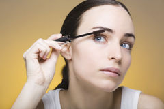 Young woman applying mascara on her self Royalty Free Stock Image