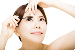 Young  woman Applying mascara isolated on white Stock Photo