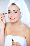 Young woman applying mascara to her eyelashes Royalty Free Stock Image