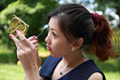 Young woman applying mascara using lash brush Royalty Free Stock Photography