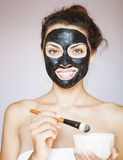 Young woman applying a mask for the face of the therapeutic blac Royalty Free Stock Images