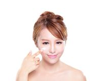 Young woman applying moisturizer cream on face. Portrait of young woman applying moisturizer cream on her pretty face isolated on white background, asian beauty Royalty Free Stock Photo