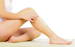 Leg Care. Young woman applying moisturizer on her leg Royalty Free Stock Photo