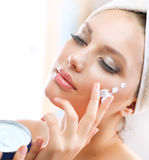 Young Woman Applying Moisturizing Cream Royalty Free Stock Photos