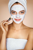 Young woman applying moisturizing facial mask. Royalty Free Stock Image
