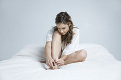 Young Woman Applying Nail Paint In Bed Royalty Free Stock Photo