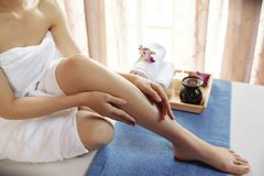 Woman applying body oil. Young woman applying oil on her body and massaging herself stock image