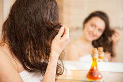 Young Woman Applying Oil Mask To Hair Tips Stock Photos