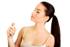 Young woman applying parfume. Stock Images