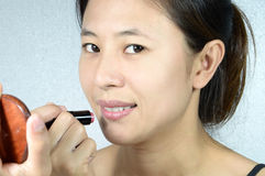 Young woman applying pink lipstick Royalty Free Stock Photos