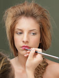 Young woman applying pink lipstick with brush Stock Photo