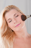 Young woman applying powder with a brush Royalty Free Stock Photo