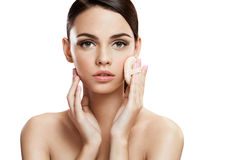 Young woman applying powdered foundation on her face with cosmetic sponge puff, skin care concept Royalty Free Stock Images